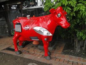 Escultura de vaca color rojo.